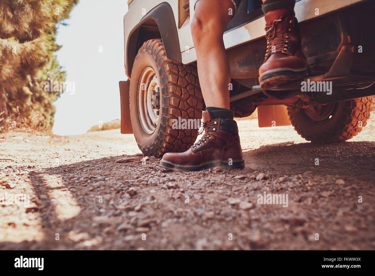 Nahaufnahme von männlichen Bein mit Lederschuh heraustreten aus einer off-Road-Fahrzeug. Auto auf dem Feldweg Stockbild