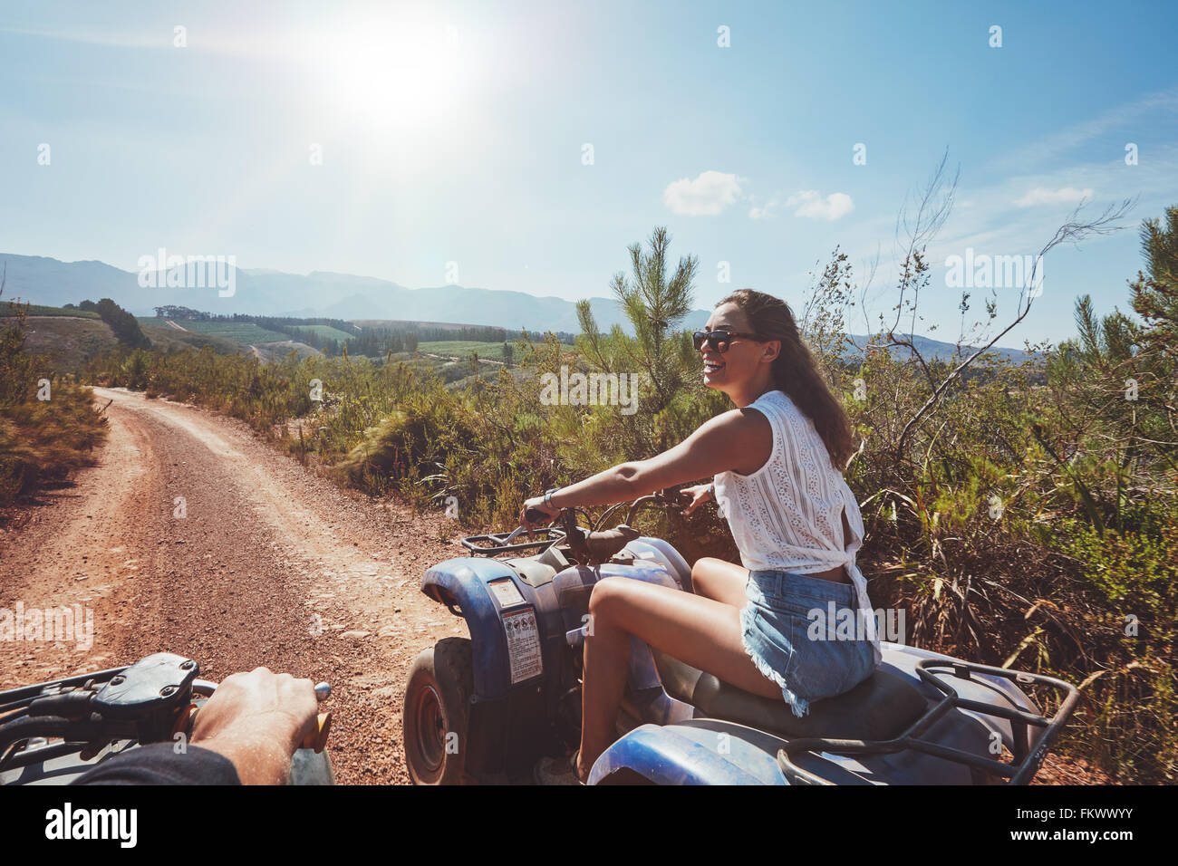 Junge Frau auf Quad-Bike auf einem Pfad. Junge Autofahrerin all-Terrain-Fahrzeug in der Natur an einem sonnigen Stockbild