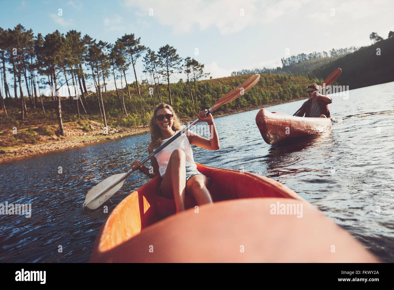 Junge Menschen an einem See paddeln. Lächelnde junge Frau Kajakfahrer mit einem Mann im Hintergrund Kajak zu Stockbild