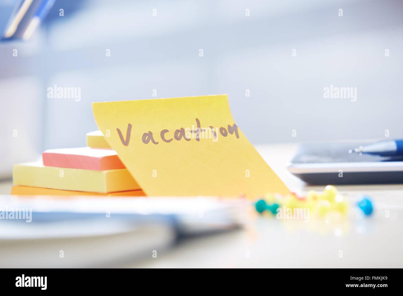 Urlaub-Text auf Klebstoff Hinweis im Büro Stockbild