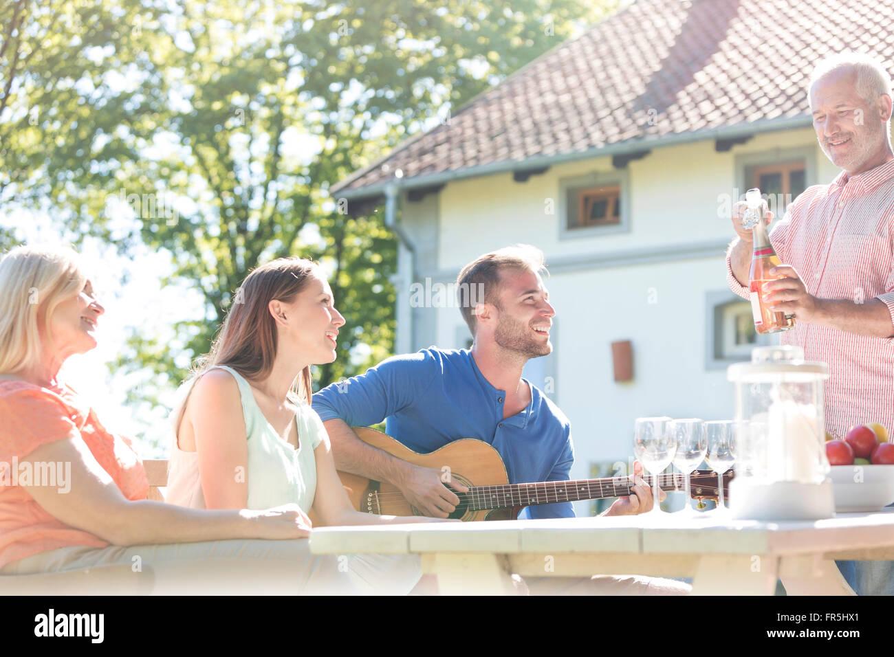 Vater Eröffnung Flasche Roséwein für Familie an sonnigen Patio Tisch Stockbild