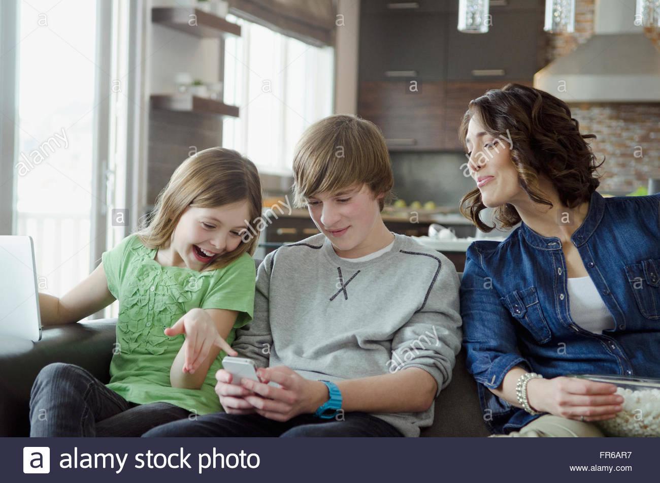 Mama und Kinder, die WiFi-Technologie gemeinsam genießen Stockbild