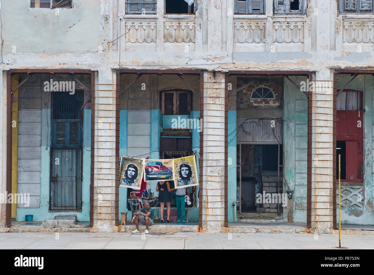 Poster von Che Guevara hängen zum Verkauf unter den verfallenden Fassaden Havannas Malecon. Stockbild