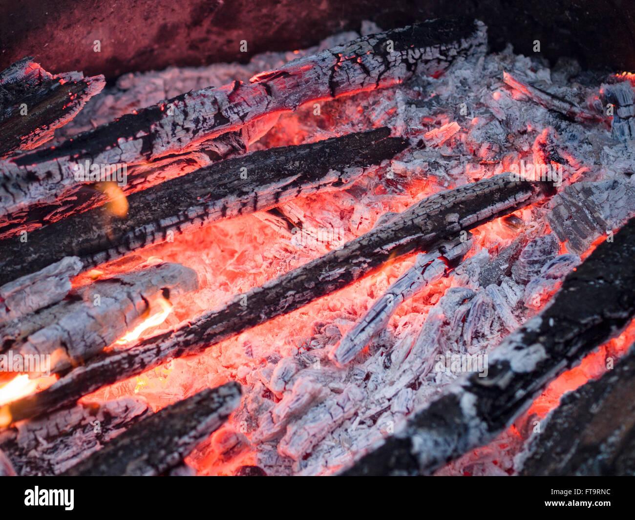 Glut in einem heißen Holzfeuer. Asche bedeckt Holz leuchtet rot in diesem Feuer abgebrannt. Stockbild