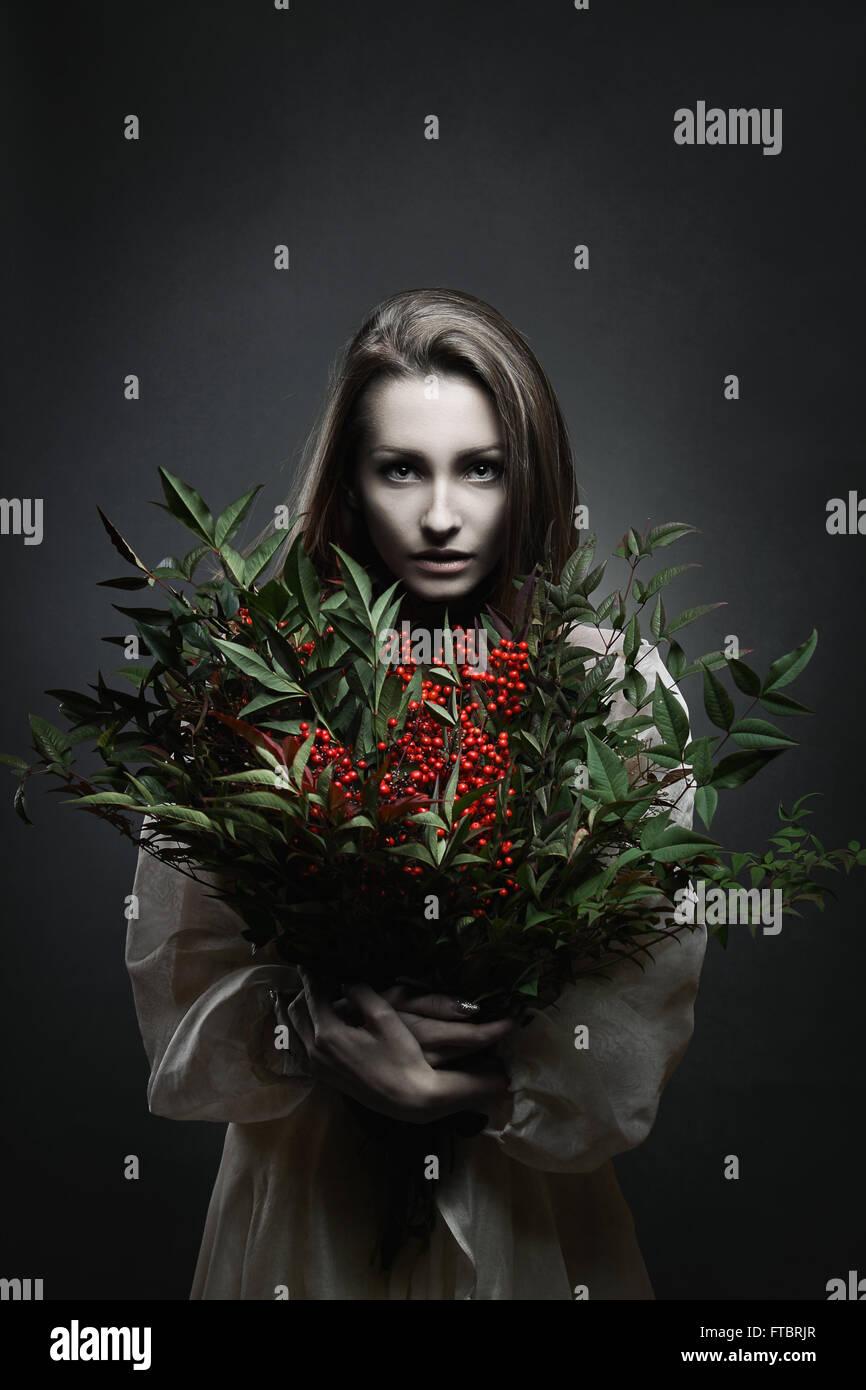 Dunkle Porträt einer schönen blasse Frau mit roten Blumen. Vampir Stockbild