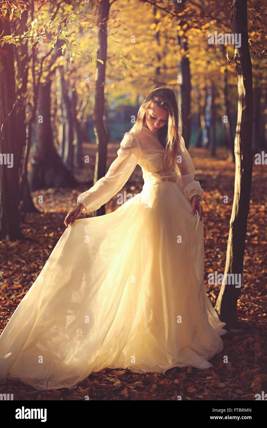 Schöne Frau mit viktorianischen Kleid im Abendlicht. Blätter im Herbst Stockbild