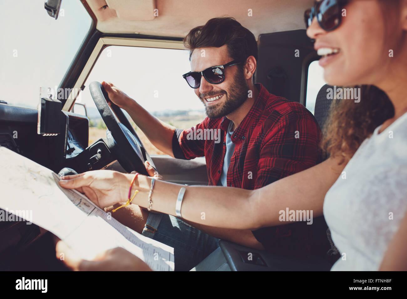 Lächelnd jungen Mann das Auto mit Frau hält einen Fahrplan zu fahren. Junges Paar auf Roadtrip. Stockbild