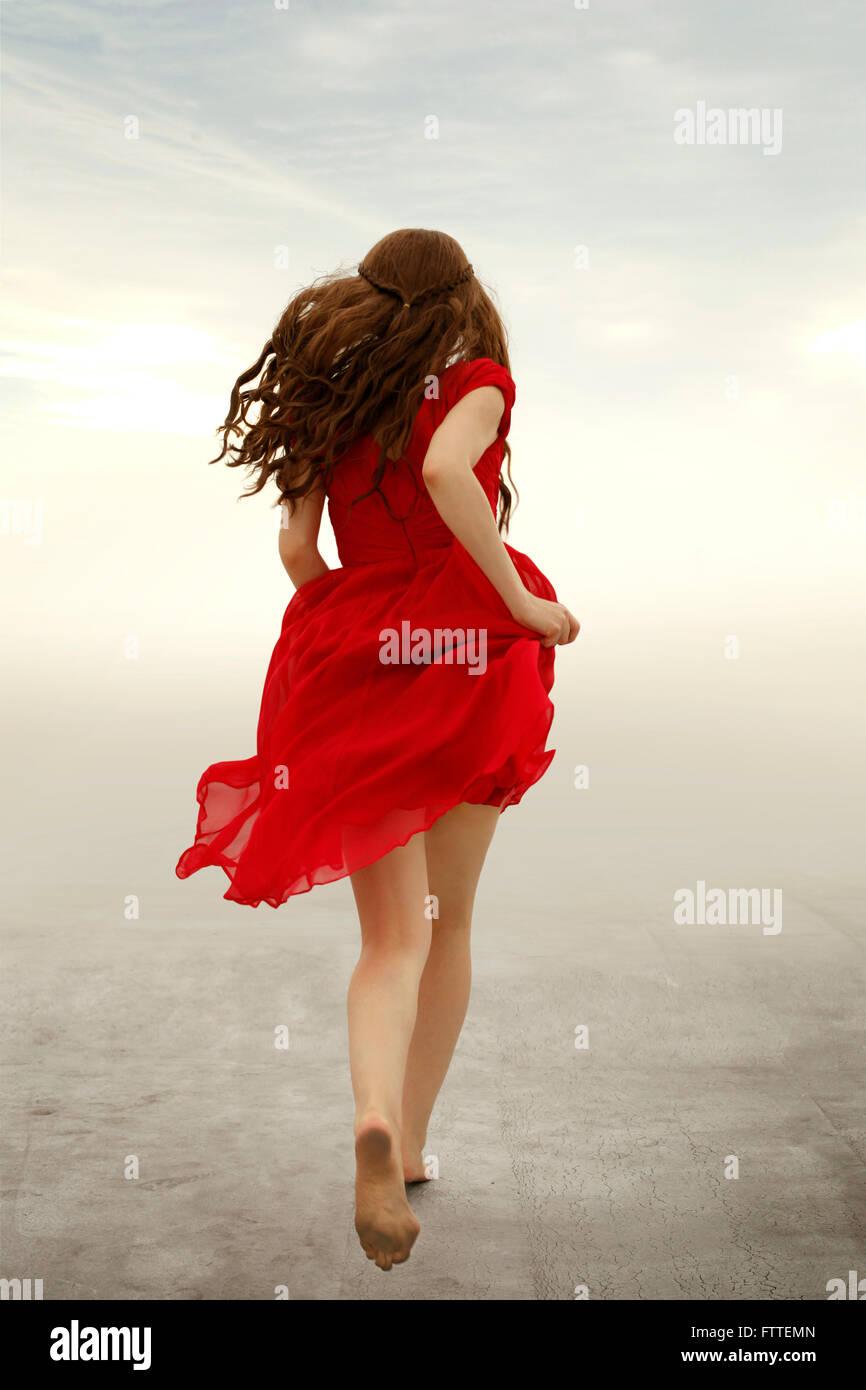 Frau im roten Kleid rennt weg Stockbild