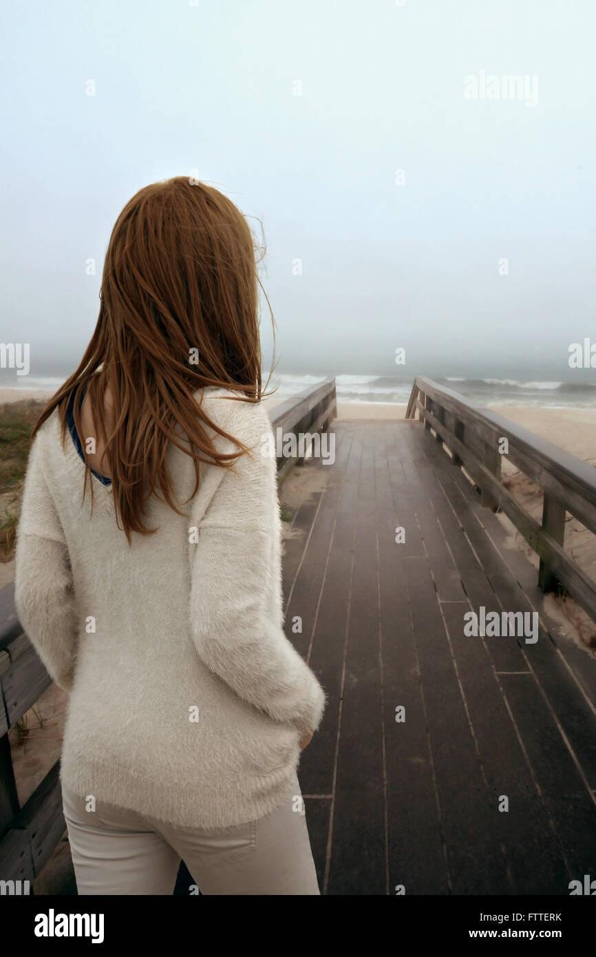 Frau zu Fuß auf Holzsteg am Strand Stockfoto