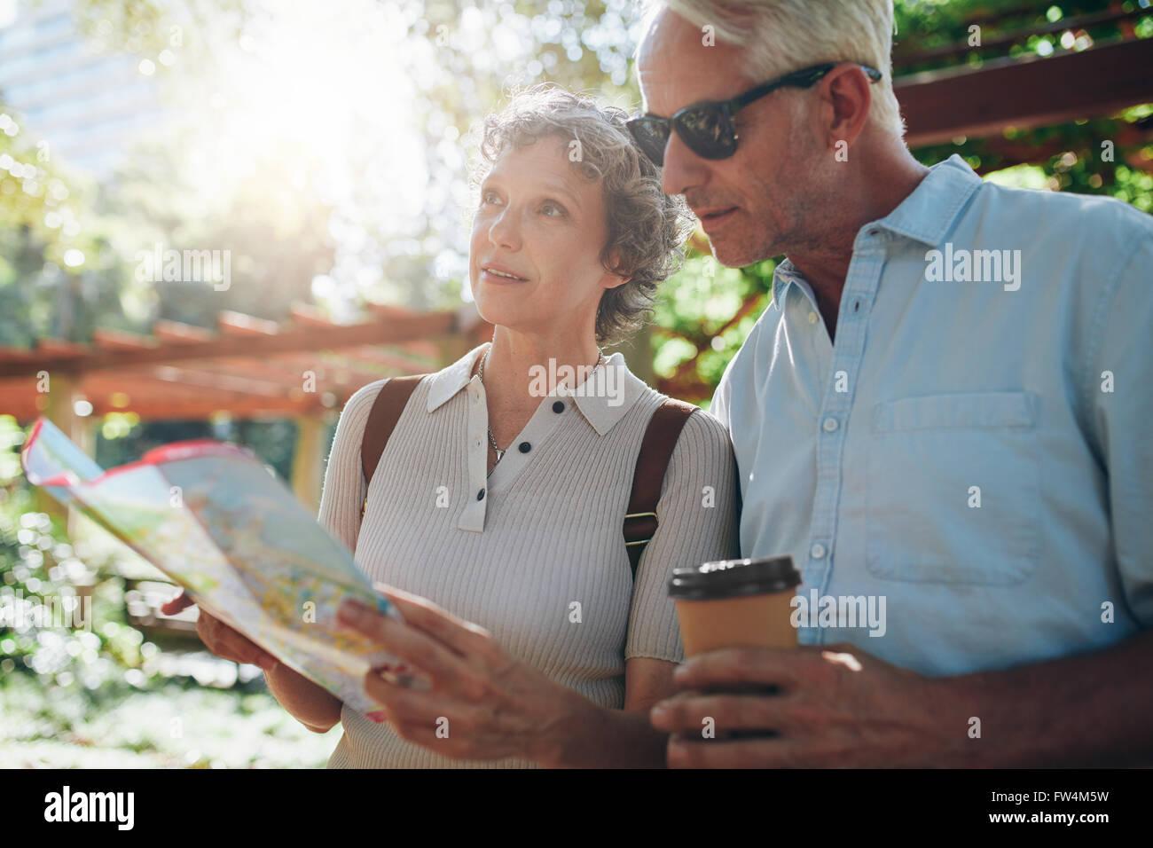 Porträt von älteres Paar mit Hilfe einer Karte nach dem Weg hautnah. Ehepaar im Ruhestand erkunden neue Stockbild