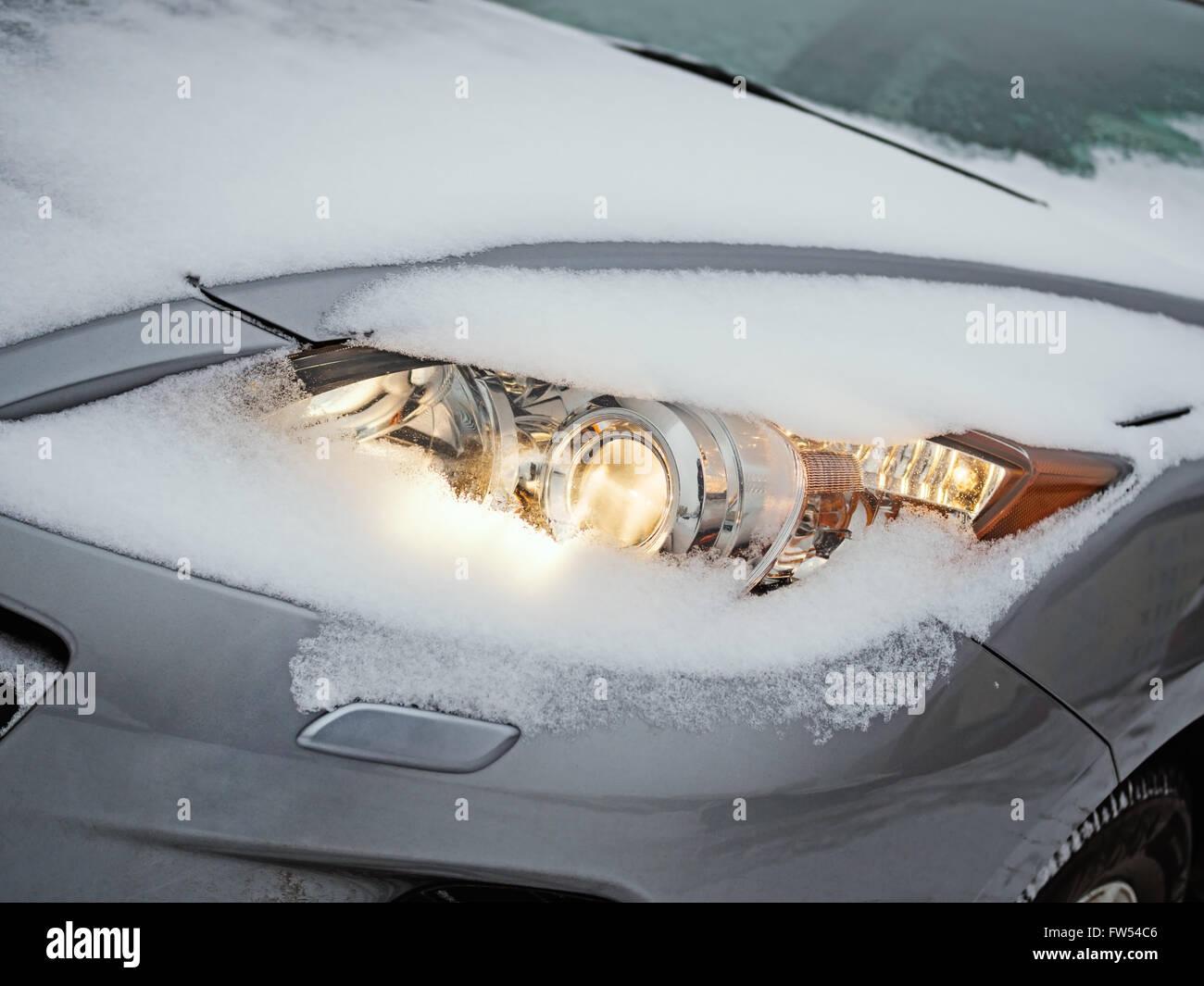 Leuchtende Scheinwerfer eines Autos mit Schnee bedeckt, wie es während eines Schneesturms gefahren wird Stockbild