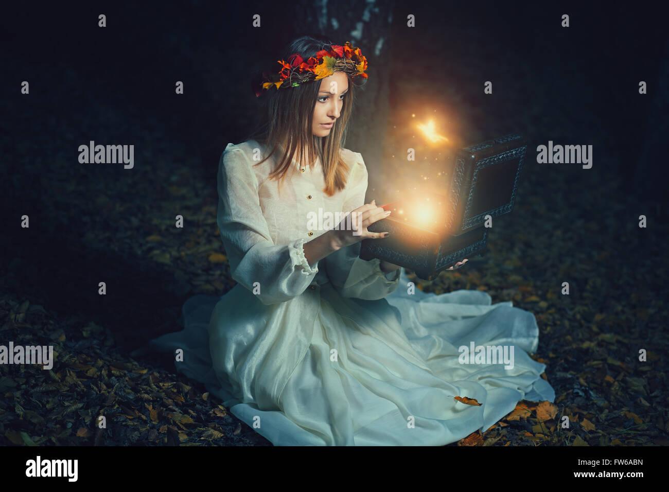 Schöne Frau öffnet eine magische Kiste voller Feen. Fantasie-Konzept Stockbild