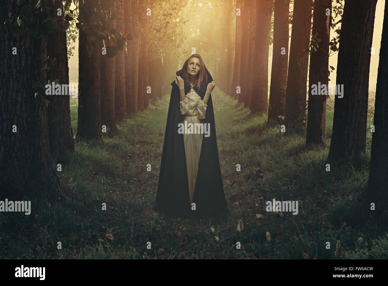 Schöne Frau mit schwarzen Robe in einem surrealen Wald Stockbild