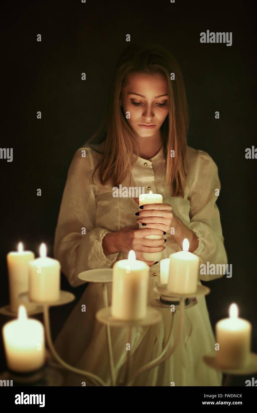 Junge Frau mit Kerze in der Hand. Gothic und surreale Konzept Stockbild