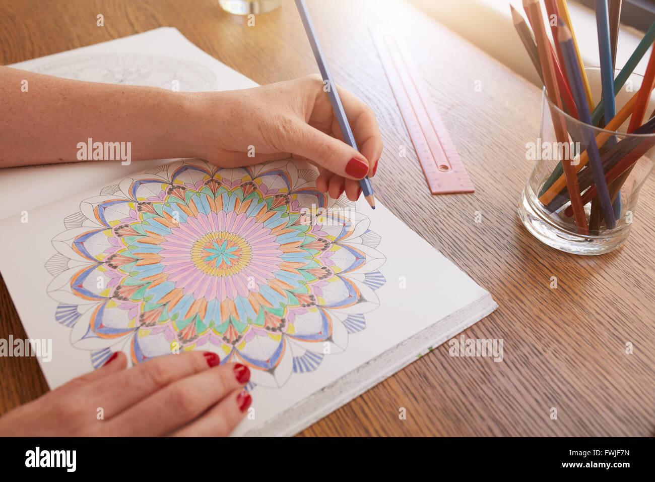 Schließen Sie herauf Bild der Frau Hände zeichnen in Erwachsene Malbuch auf einem Tisch zu Hause. Stockbild