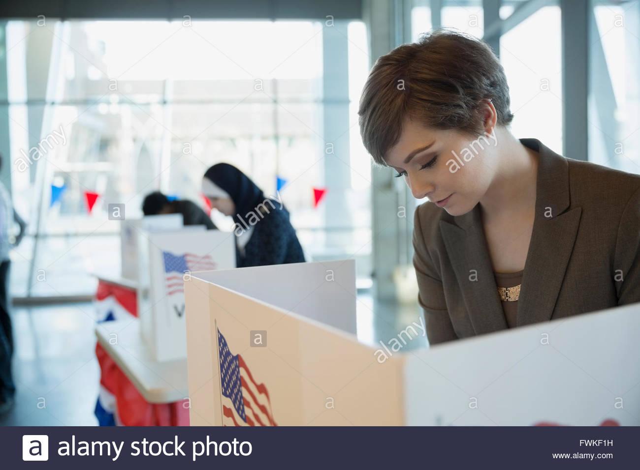 Junge Frau bei der Abstimmung stand im Wahllokal Stockbild