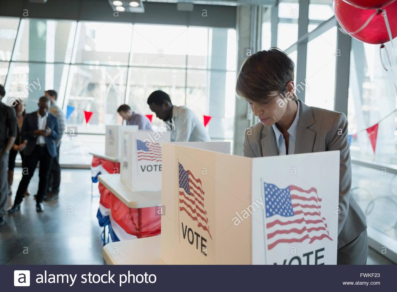 Frau bei der Abstimmung stand im Wahllokal Stockbild