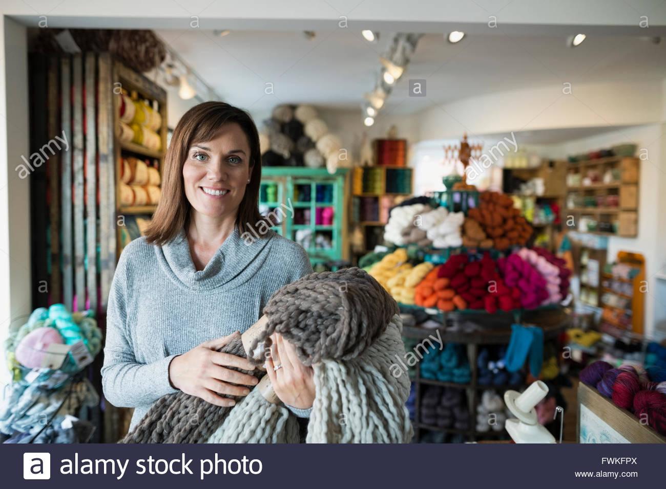 Porträt zuversichtlich Garn Ladenbesitzer halten gestrickte decken Stockbild