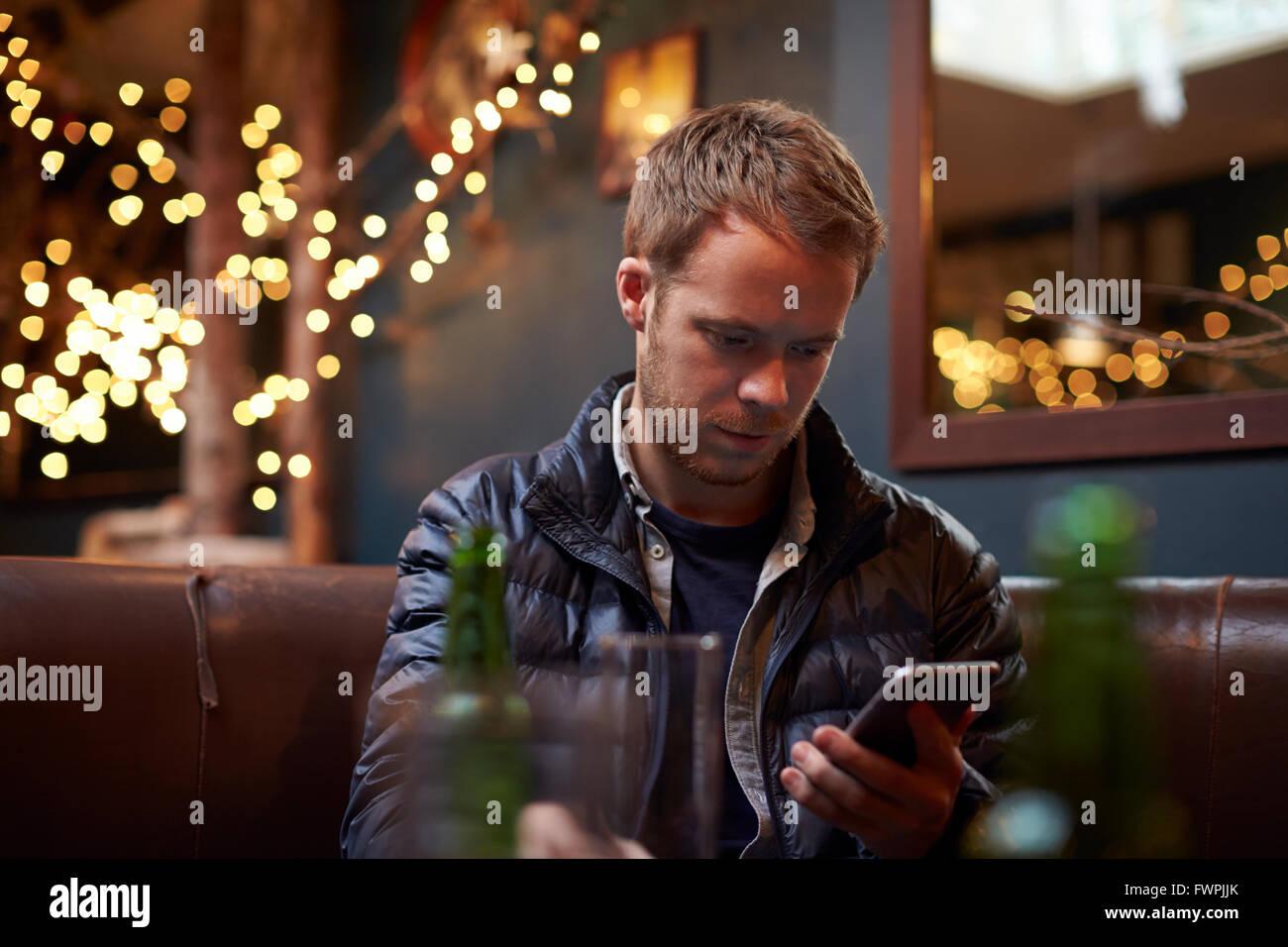 Mann sitzt im Cafe SMS Stockbild