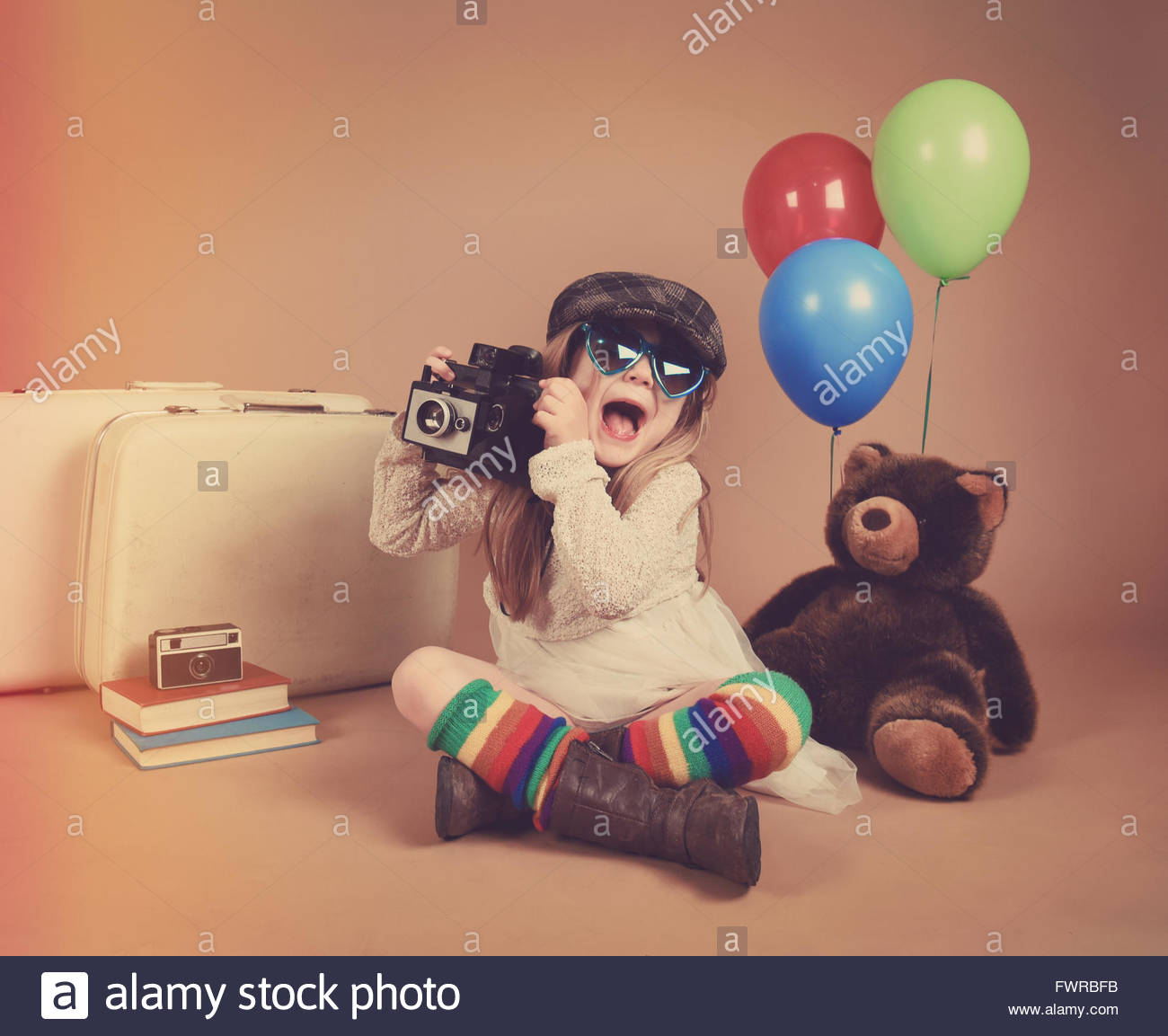 Ein Foto eines Vintage Kindes aufnehmen eines Bildes mit einer alten Kamera mit Luftballons und ein Teddybär Stockbild