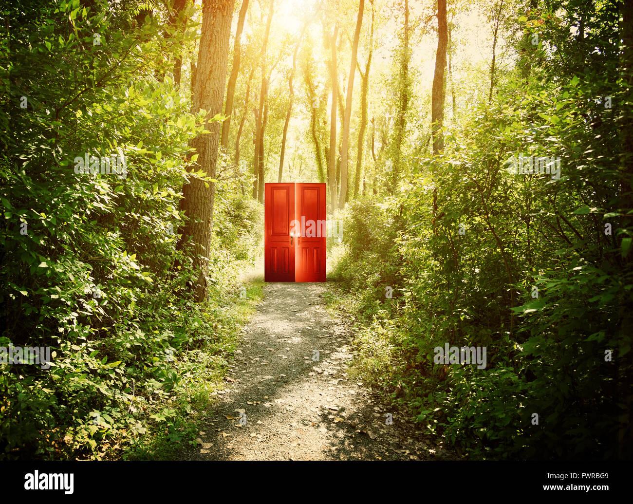 Eine rote Tür ist auf einem Trail im Wald mit Bäumen für eine konzeptionelle Konzept über glauben, Stockbild