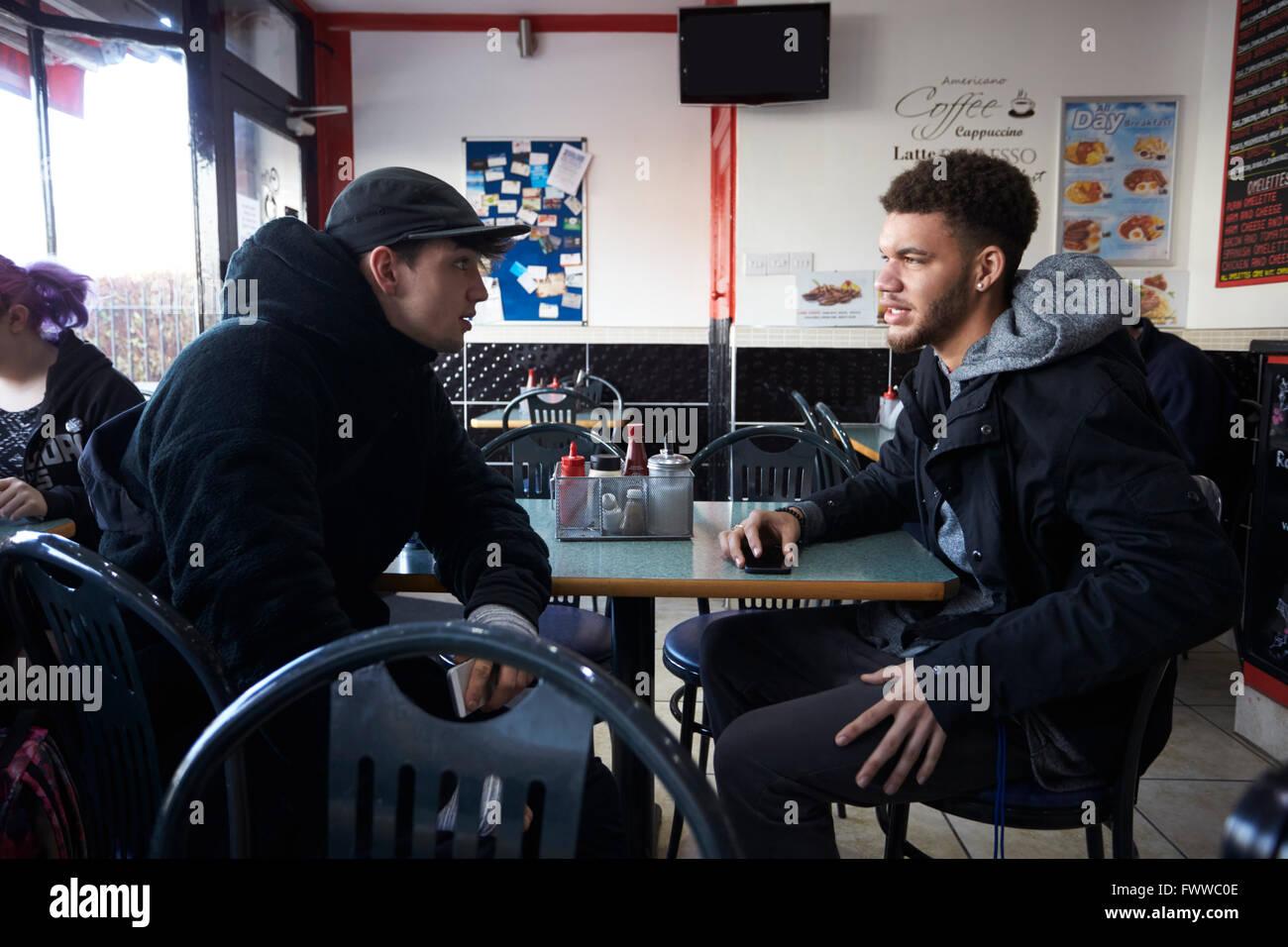 Zwei männliche Studenten Essen im Café Stockbild