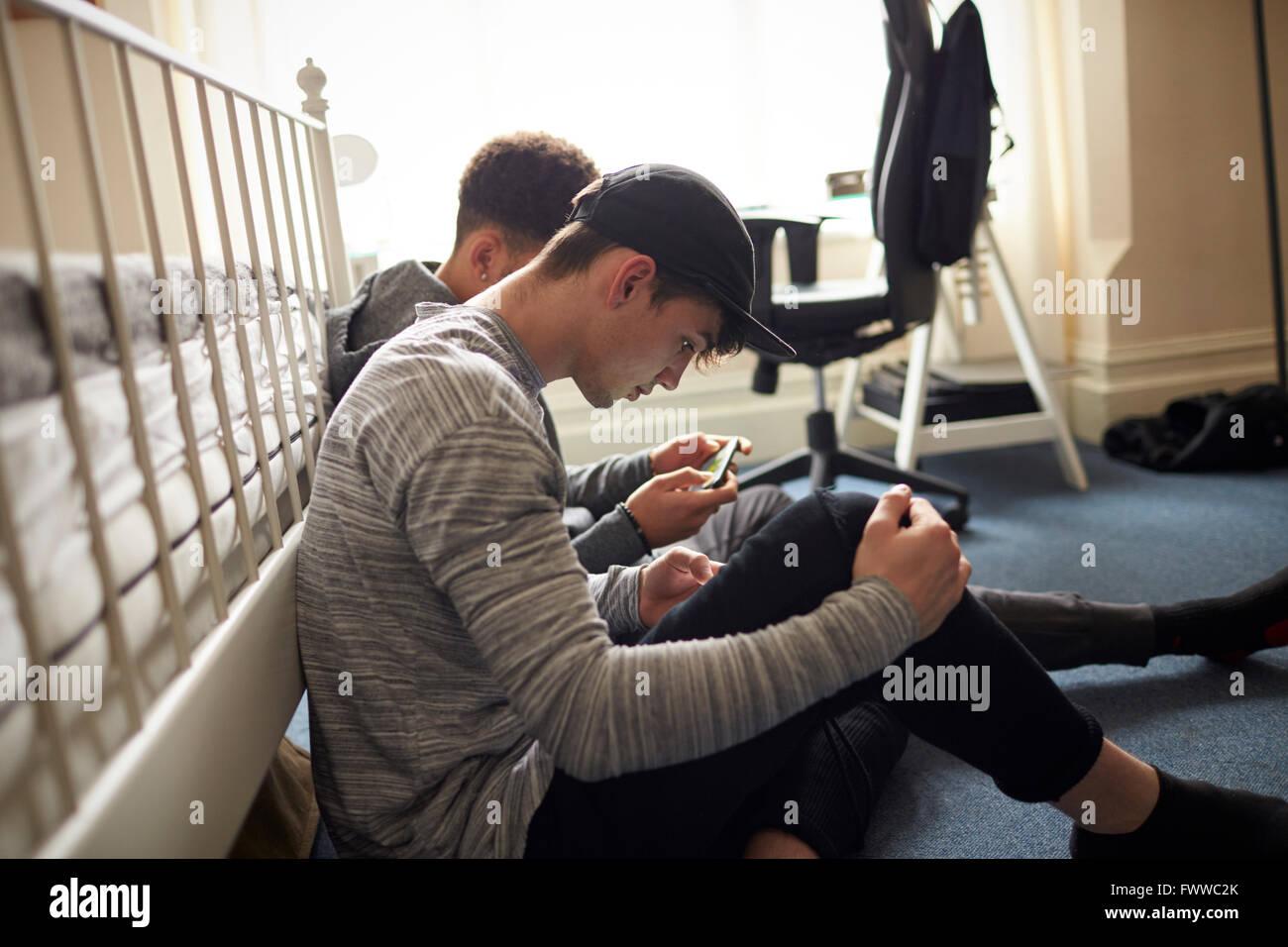 Zwei männliche Studenten im Schlafzimmer überprüfen Sie Nachrichten auf dem Handy Stockfoto