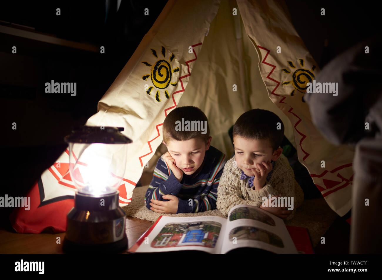 Zwei jungen lesen im Zelt drinnen einrichten Stockbild