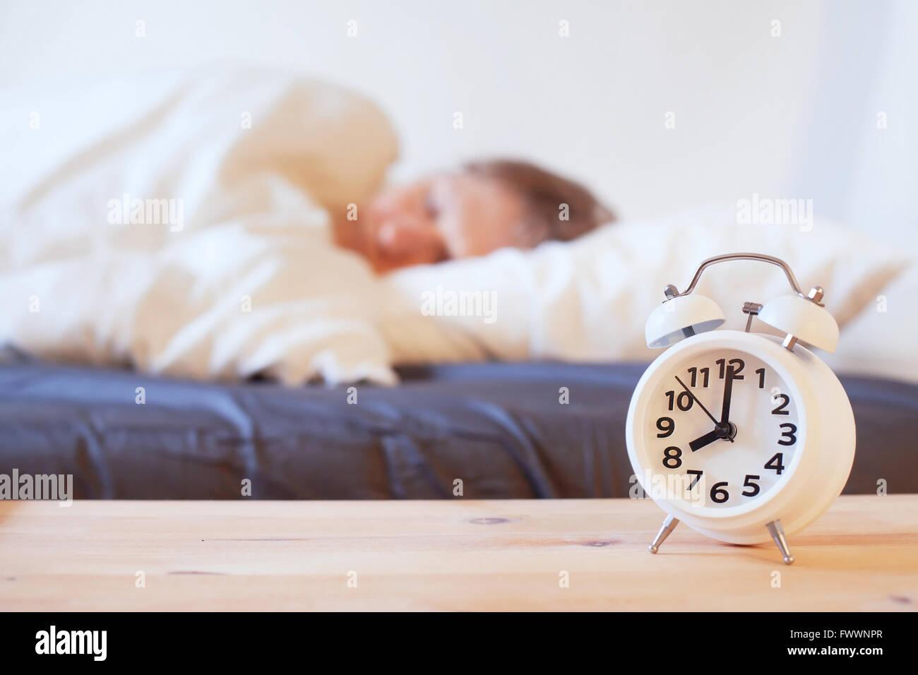 Wachen Sie am Morgen mit Wecker, Person schlafend im Bett auf Stockbild