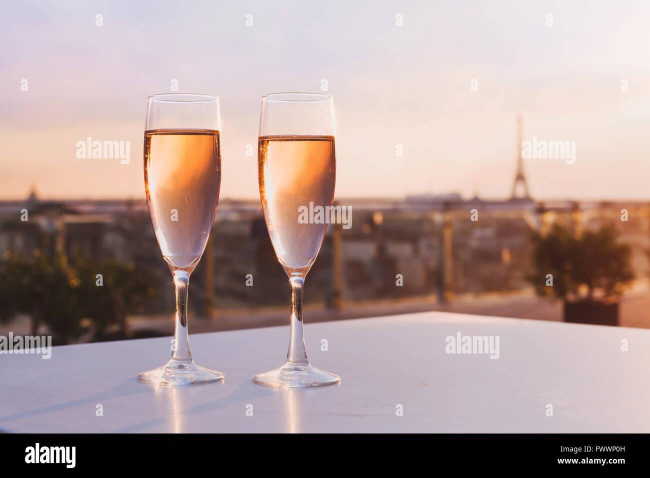 zwei Gläser Champagner im Restaurant auf der Dachterrasse mit Blick auf Eiffelturm und Paris Skyline, Luxus Stockbild