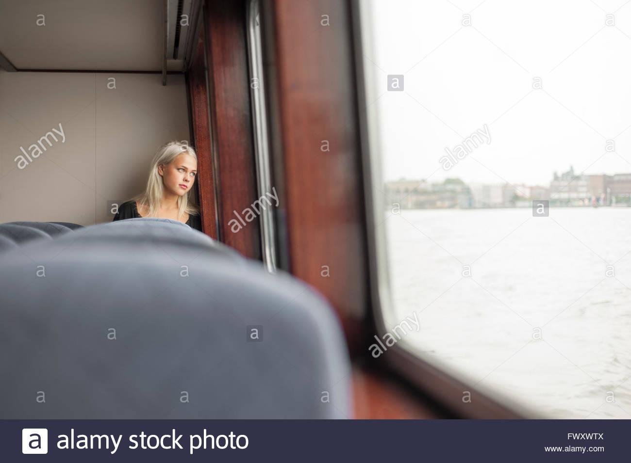 Schweden, Vastra Gotaland, Göteborg, junge Frau, die durch Fenster in Zug Stockbild
