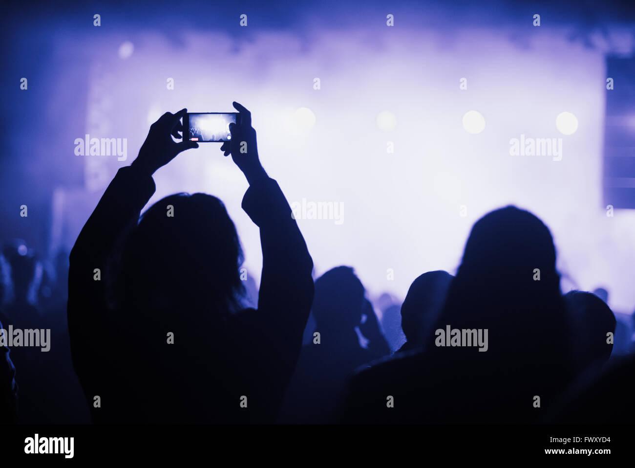 Finnland, Helsinki, Uusimaa, Frau mit Smartphone-Konzert Stockbild