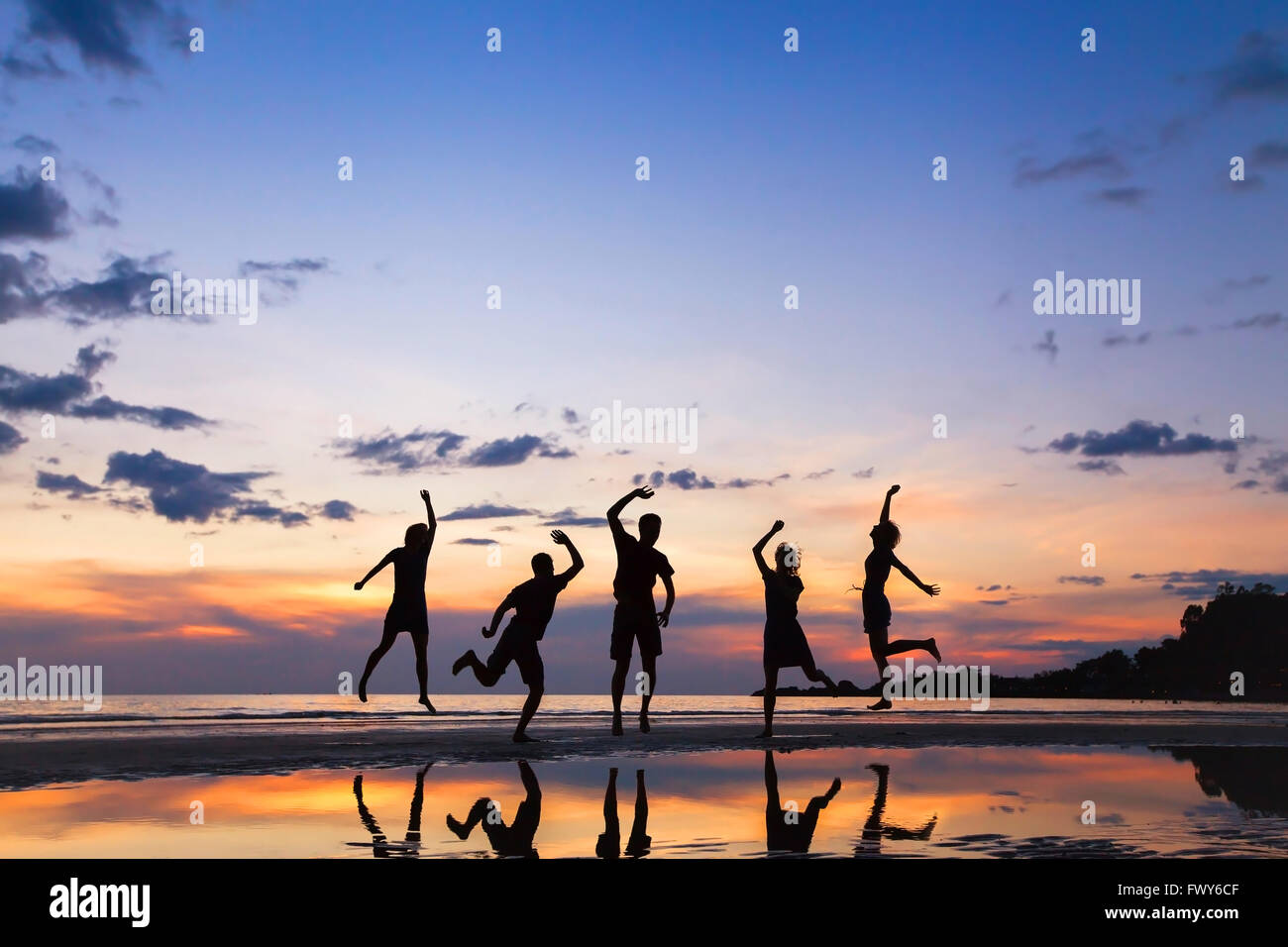Gruppe von Menschen springen am Strand bei Sonnenuntergang, Silhouette von Freunden gemeinsam Spaß haben Stockbild