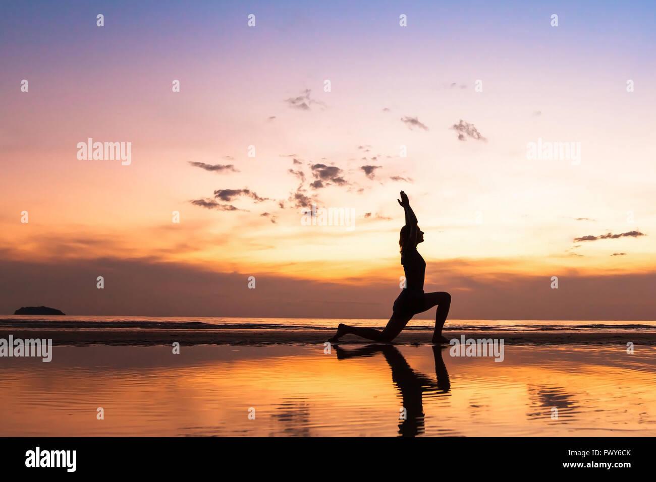 schöne Yoga üben am Strand bei Sonnenuntergang, Hintergrund mit Exemplar Stockbild