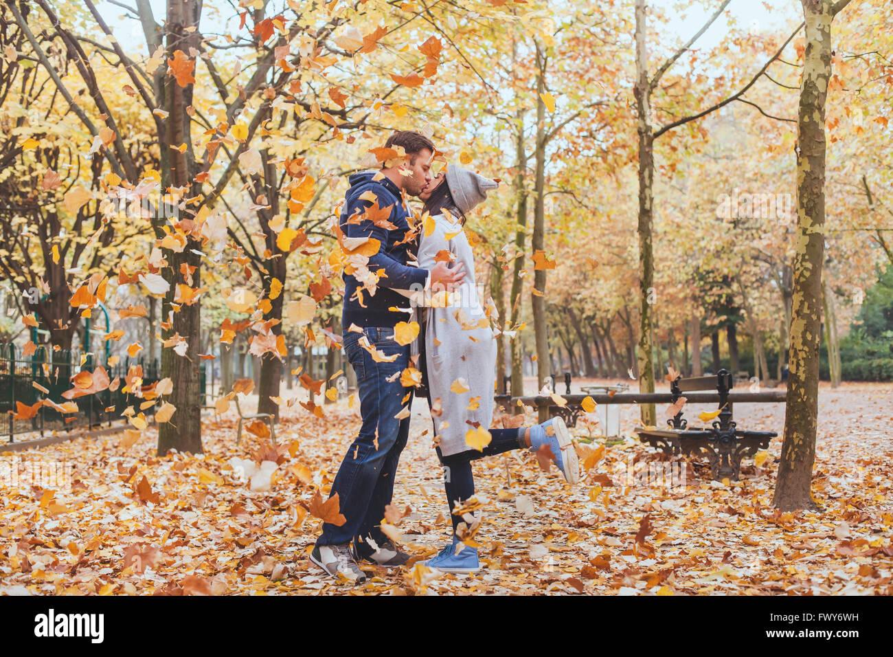 Herbst Kuss, junge Liebespaar im Park mit fallenden Blätter Stockbild
