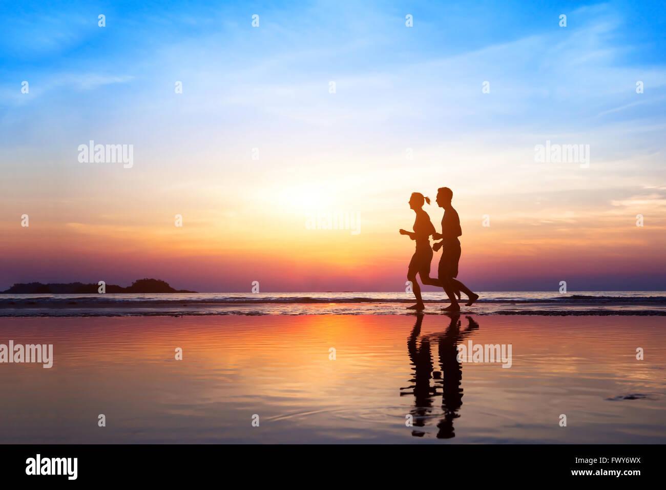 Training-Hintergrund, zwei Menschen, Joggen am Strand bei Sonnenuntergang, Läufer Silhouetten, gesunden Lebensstil Stockfoto