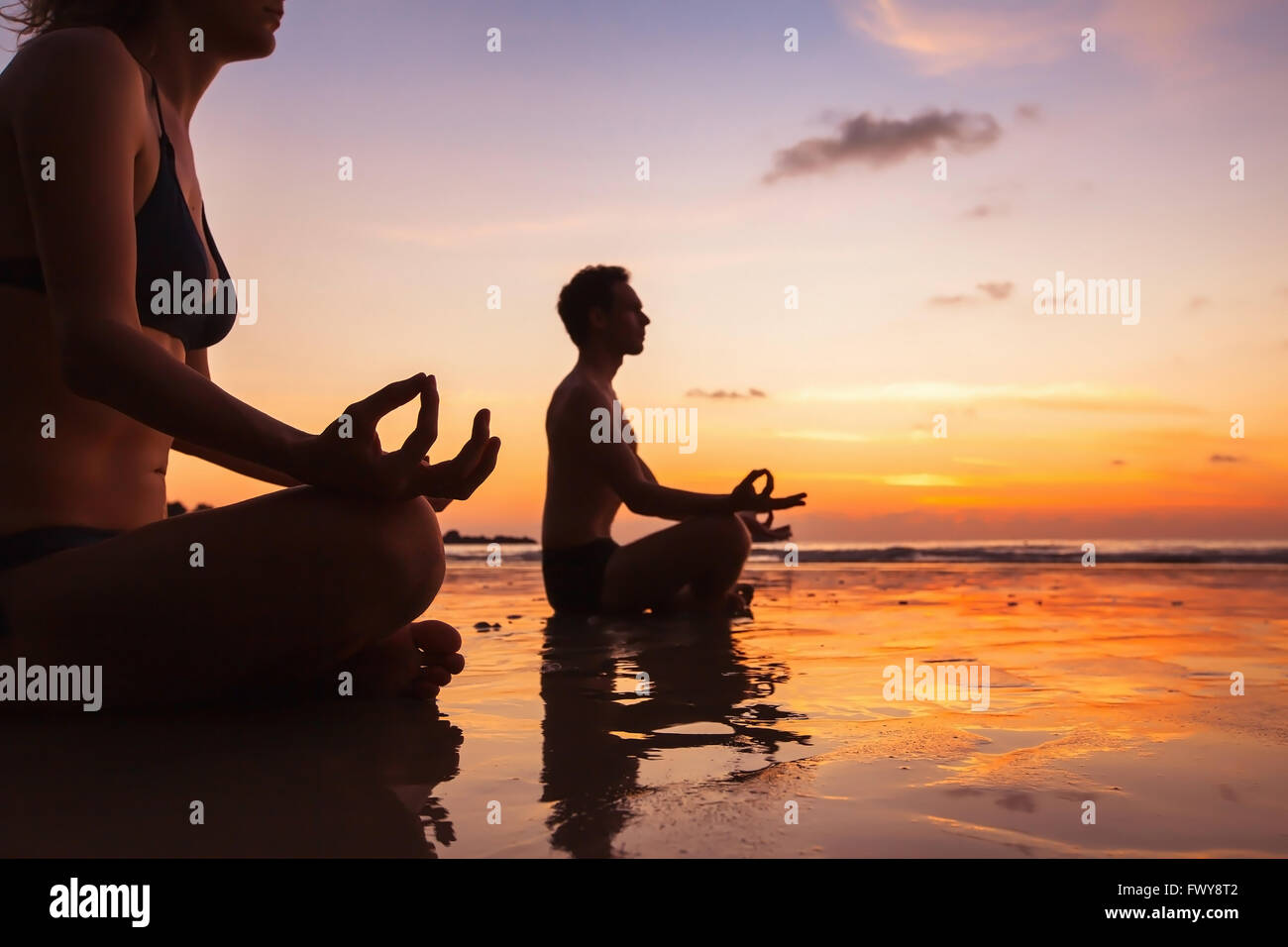 Gruppe von Menschen, die meditieren auf dem Strand, Yoga und Gesundheit Hintergrund Stockbild
