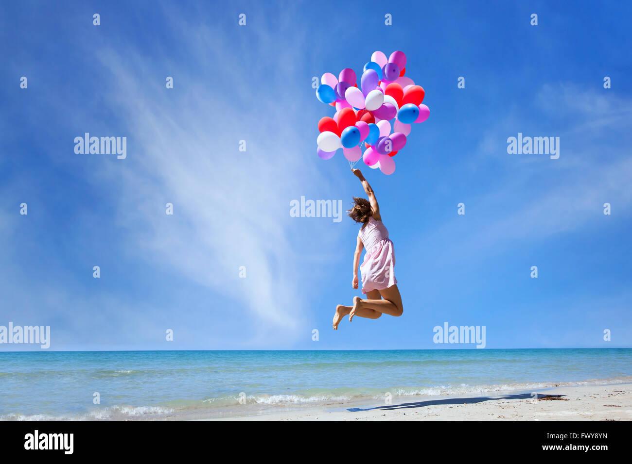 Traum Konzept, Mädchen fliegen auf bunte Luftballons in den blauen Himmel, Phantasie und Kreativität Stockbild