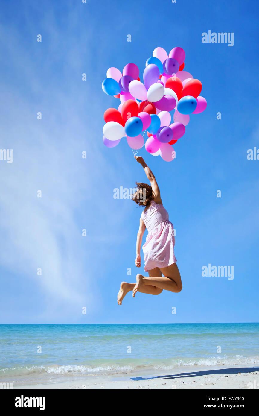 Inspiration, glückliche Menschen, Frau fliegen mit bunten Luftballons in den blauen Himmel, kreatives Konzept Stockbild