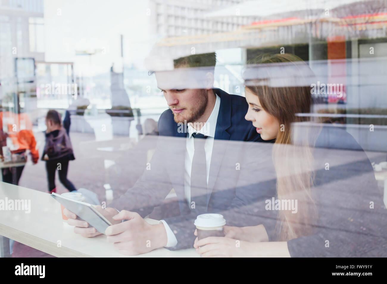 Geschäftsleute im Café auf den Bildschirm des Tablets Stockbild