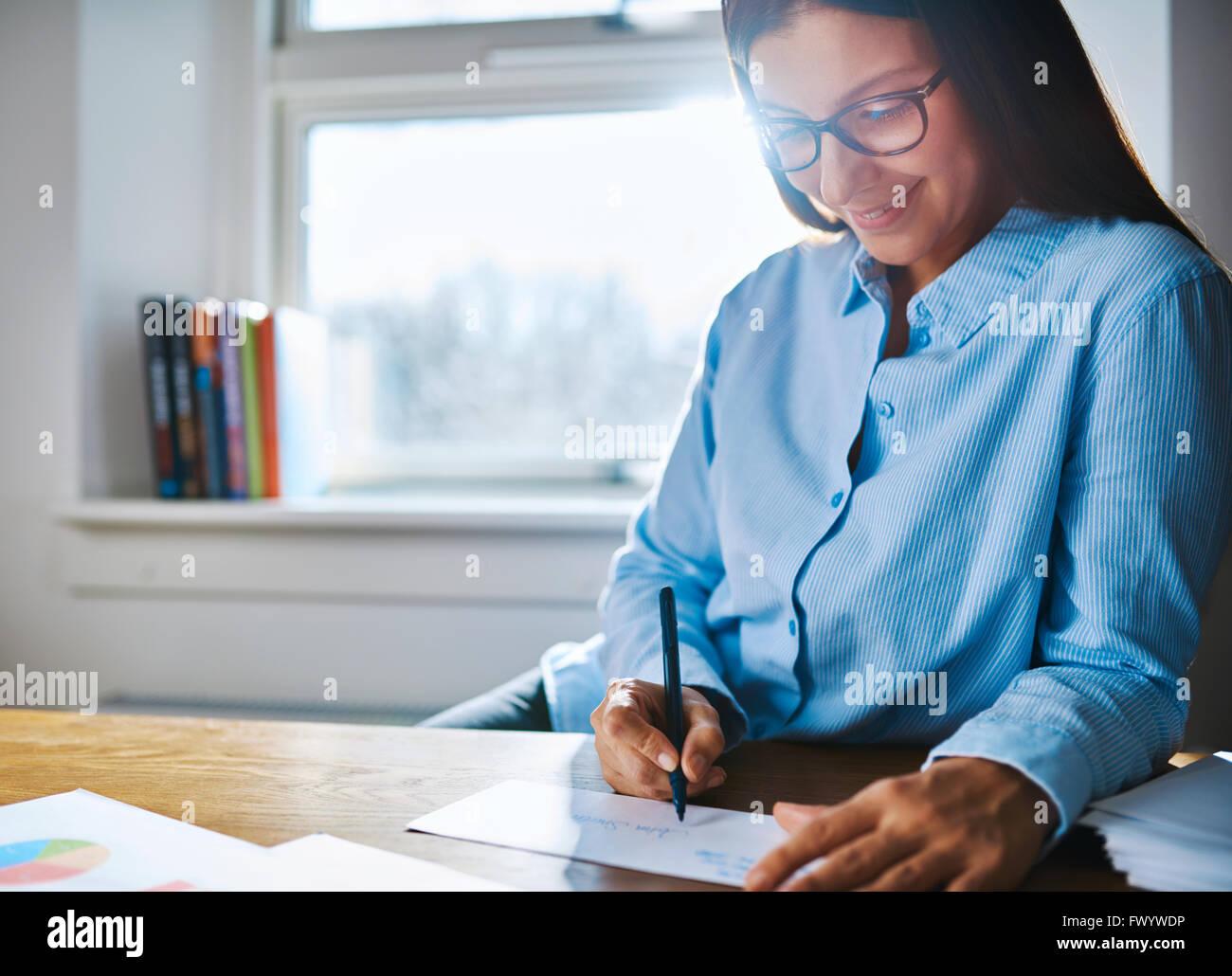 Selektiver Fokus Nahaufnahme auf happy Unternehmer weibliche Brille und blaue T-Shirt am Schreibtisch schreiben Stockbild