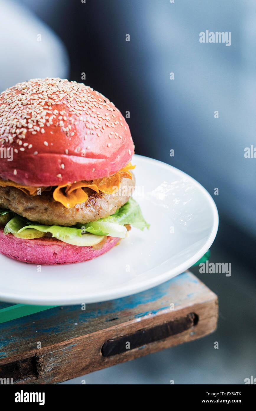 Chicken Burger mit Gurken und Chips in rote Beete Brot Brötchen Stockbild