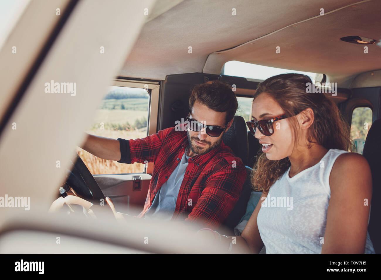 junges paar in ihrem auto sitzen und mit blick auf etwas. Black Bedroom Furniture Sets. Home Design Ideas