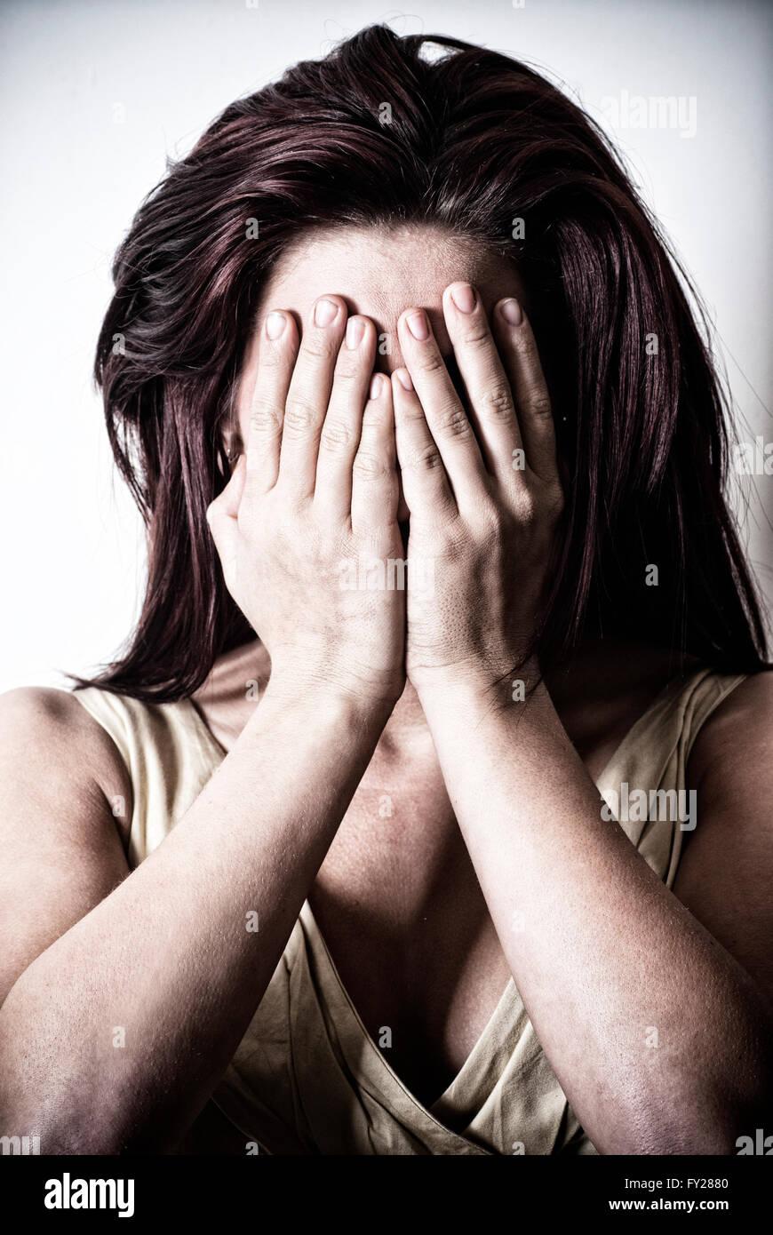 Junge Frau Gesicht mit den Händen versteckt Stockbild