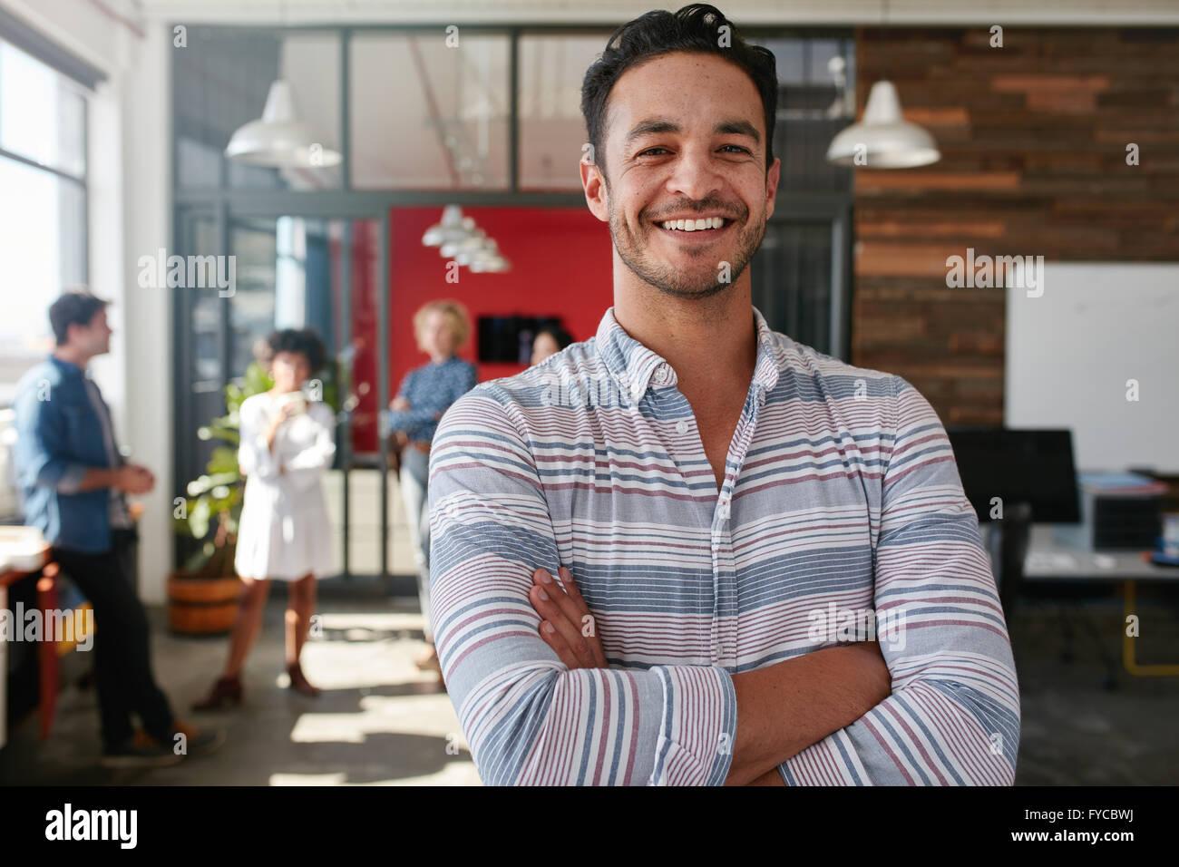 Porträt eines schönen jungen Geschäftsmannes Stand mit verschränkten in einem Büro. Intelligente Stockbild
