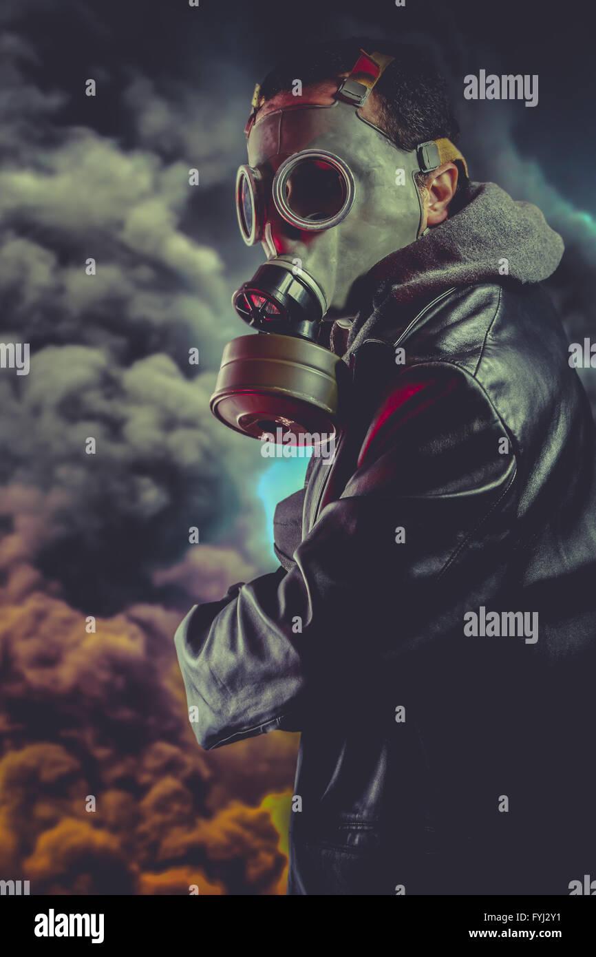 Bewaffneter Mann mit Gasmaske über Explosion Hintergrund Stockfoto