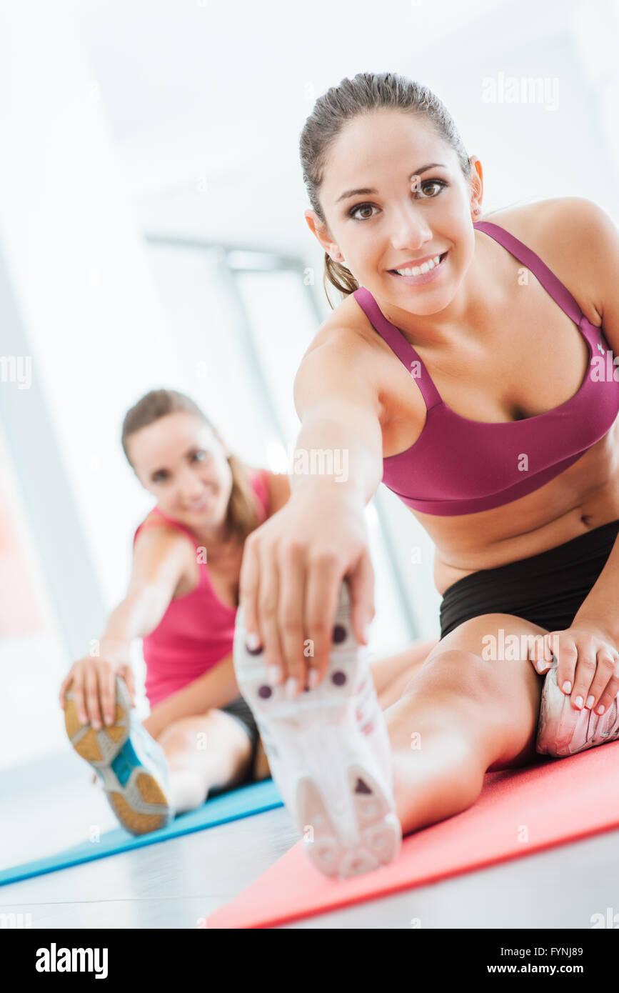 Lächelnde junge Frauen in der Turnhalle eine stretching-Übung für die Beine auf eine Matte, Fitness Stockbild
