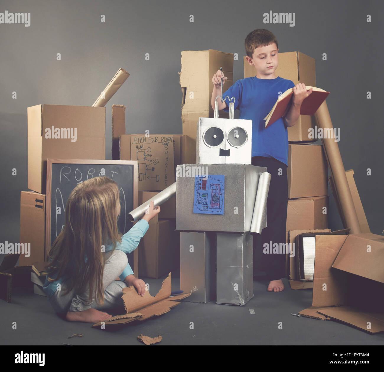 Zwei Kinder bauen einen Metall Roboter aus Pappkartons mit Werkzeugen und Bücher für eine Fantasie, Wissenschaft Stockbild