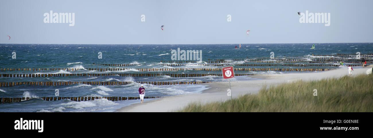 Sandstrand mit hölzernen Buhnen und Kitesurfer Stockbild