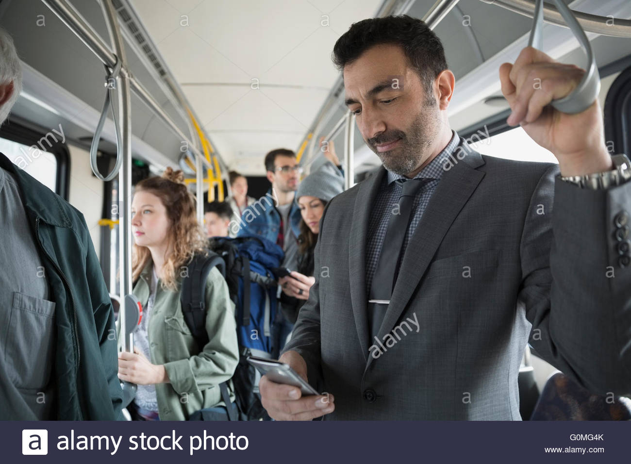 Geschäftsmann SMS Handy steht auf bus Stockbild